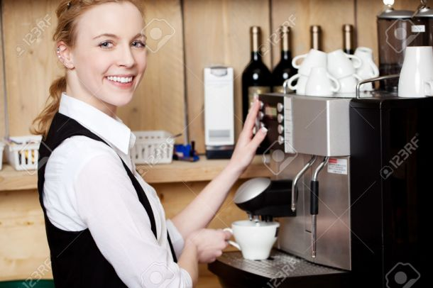 Waitress Filling Coffee In Cup From Machine At Cafe